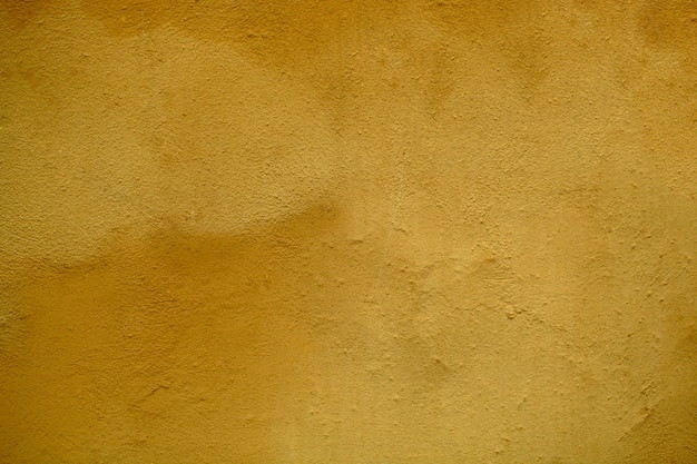 Weathered stained ochre wall  texture with rough plaster finish in close up in a full frame view.