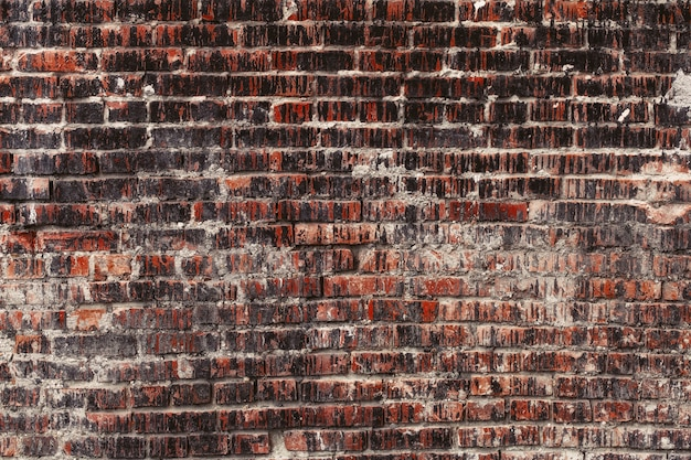Weathered stained old dark brick wall, texture grunge background