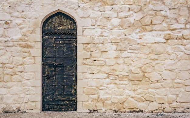 東洋の彫刻が施された古い金属製のドアが付いた風化した石の壁。