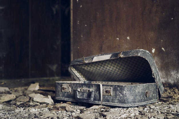 Weathered suitcase inside an abandoned destroyed house