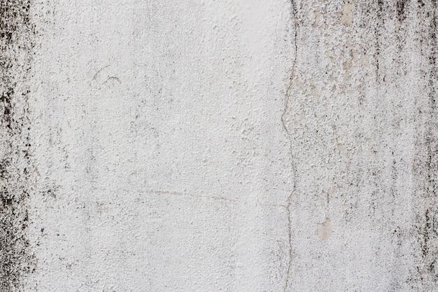 Устойчивая белая штукатурная стена с черными полосками из плесени и грибов по бокам
