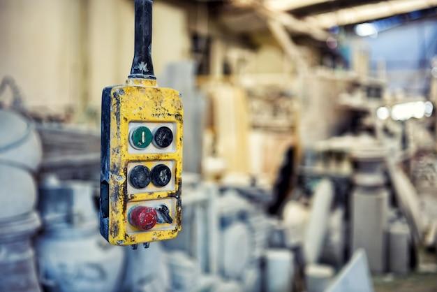 흐릿한 장비가 있는 산업 작업장에 매달려 있는 원격 작동 오버헤드 크레인용 버튼이 있는 풍화된 노란색 컨트롤러