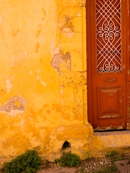 Weathered yellow wall in rhodes greece