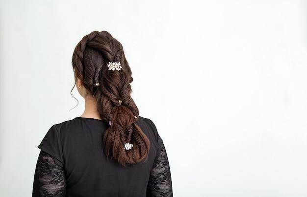 織り、三つ編みのテールのヘアスタイル。ロングヘアの茶髪の女性の髪型