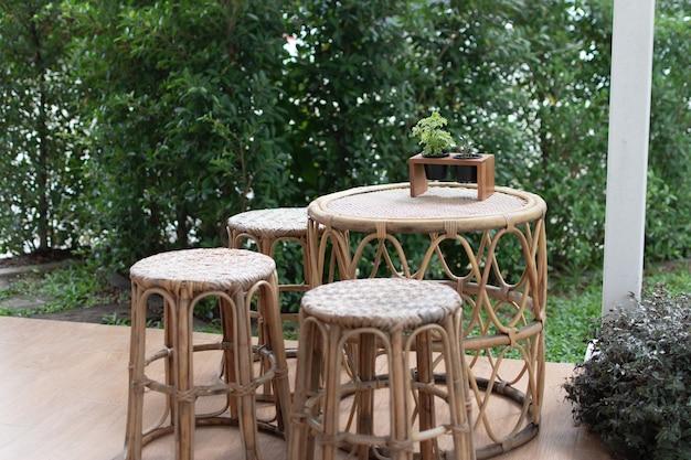 庭の木の床にセットされた織りの木製テーブル