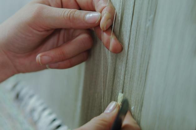Ткачество и изготовление ковров ручной работы крупным планом. женские руки ткут ковер