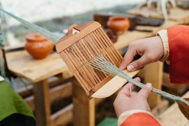 직조 공예. 전통적인 복장에있는 여자는 손으로 작동합니다.