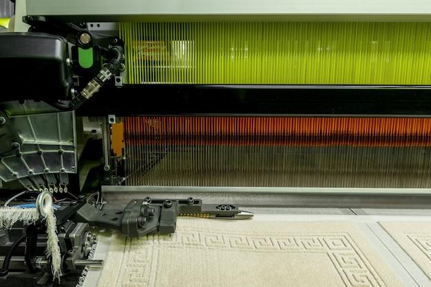 繊維工場で織機、クローズアップ。工業用生地の生産ライン