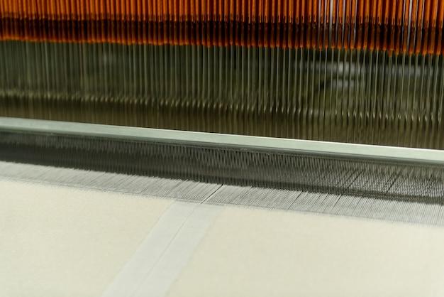 Ткацкий станок на текстильной фабрике, крупным планом. линия по производству промышленных тканей