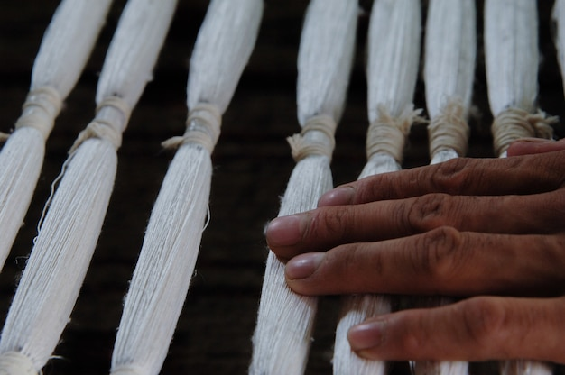 Weaving and manufacturing of yarn closeup. the hand holds ready-made yarn