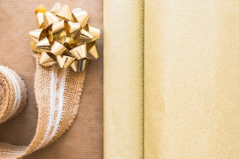 Weaving ribbon and golden bow with shiny gift paper