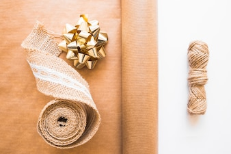 Weaving ribbon; golden bow; brown gift paper and jute string on white background