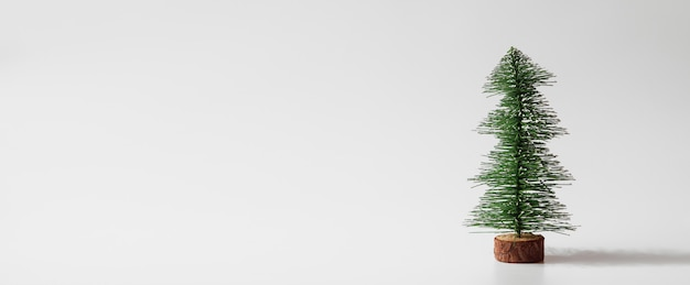Web banner miniature christmas tree on white background with copyspace