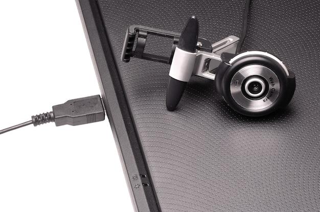 Веб-камера, лежащая на черном закрытом ноутбуке