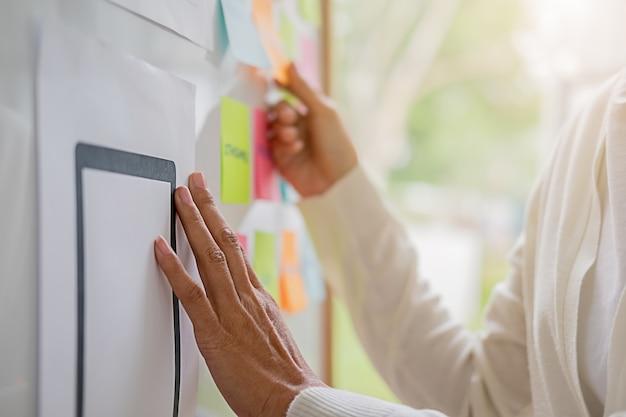 전략 계획을위한 브레인 스토밍을하는 웹 디자이너. 사무실 보드에 할 일이 다채로운 스티커 메모. 사용자 경험 (ux)