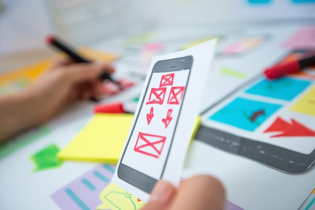 Web designer is developing an application for mobile phones. creating a layout of the user interface functions of smartphones.
