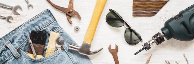 フラットレイアウトアクセサリーツールとwebバナーのさびた白い木製の労働者のための服。労働または労働日、労働者の日、父の日、およびホームdiyの修理のためのトップビューwebバナーのコンセプト。