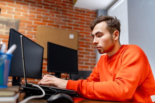 Веб-программист возле монитора в офисе компании по разработке программного обеспечения. технологии программирования и кодирования веб-сайтов.