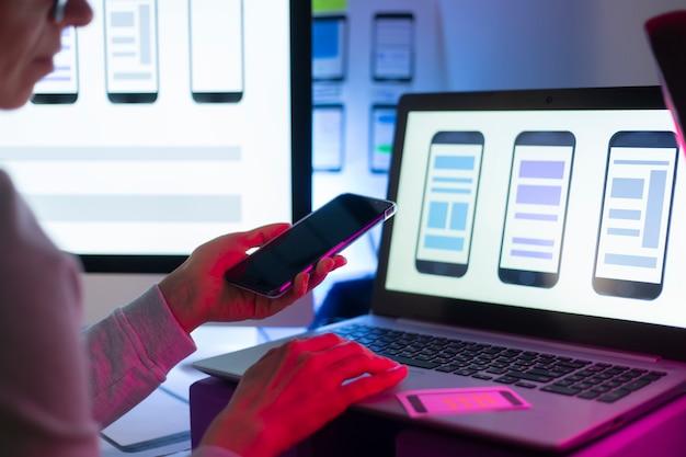 Дизайнеры веб-интерфейса разрабатывают приложение для смартфонов. команда создателей работает над интерфейсом для мобильных телефонов.