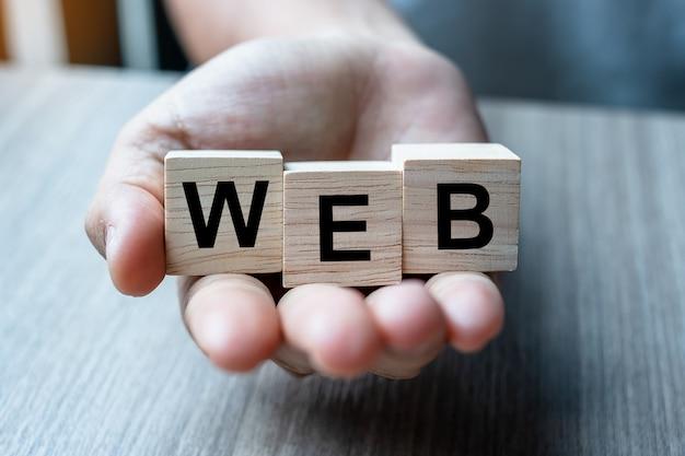 Webビジネス単語の木製キューブブロックを持っているビジネスマン手。 webサイト、ネットワーク、データベース、およびマーケティングの概念