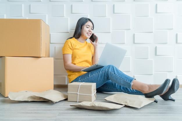 若いアジアのビジネスは、コンピューターを使用して電子メールまたはwebサイトから顧客の注文をチェックし、パッケージを準備するためのオンライン販売者の所有者を立ち上げ