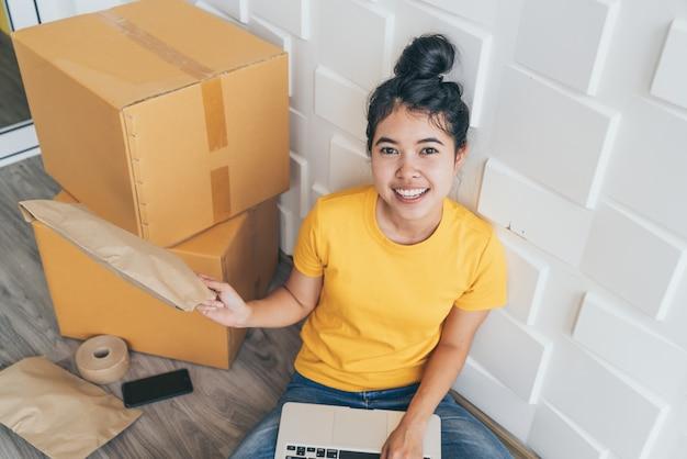 若いアジアのビジネスは、電子メールまたはwebサイトから顧客の注文をチェックし、パッケージを準備するためにコンピューターを使用してオンライン販売者の所有者を立ち上げます