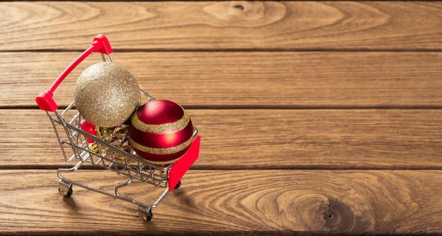 Webバナーの木材の上のミニチュアショッピングカートにクリスマス飾りボール