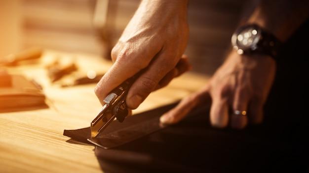 革工房での革ベルトの作業工程。男持株ツール。古い皮なめし工場のタナー。木製テーブルの表面。男の腕を閉じます。テキストとデザインの暖かい光。 webバナーサイズ