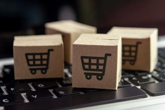 オンラインショッピング-ノートパソコンのキーボードにショッピングカートのロゴが入った紙パックまたは小包。オンラインweb上のショッピングサービスおよび宅配便を提供しています。