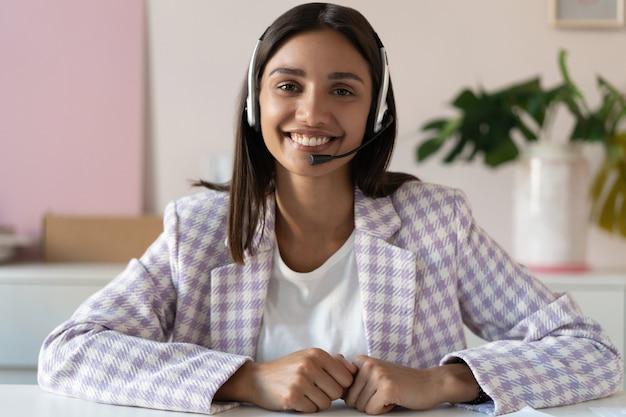 웹캠 보기 인도 혼혈 여성이 화상 회의 애플리케이션을 사용하여 실내에 앉아 이야기하고 있습니다.