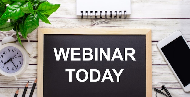 Webinar today written on a black background near pencils, a smartphone, a white notepad and a green plant in a pot