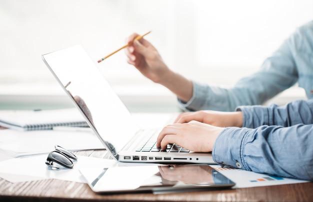 Разработчики веб-сайтов работают с ноутбуком в офисе на деревянном столе. эффект фильма