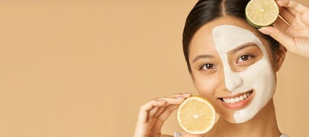 Заголовок веб-сайта красоты портрет молодой женщины с лицевой маской, нанесенной на половину