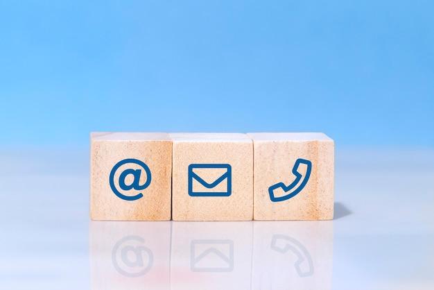 ウェブサイトのページは私達に連絡するか、または電子メールのマーケティングの概念。木製のブロックとシンボルのアドレス、電子メール、電話のコンセプト