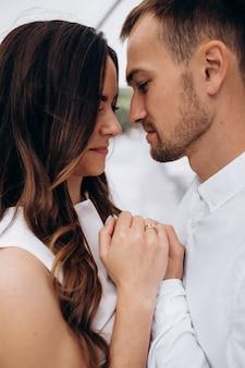 暗い夏の日に傘の下で美しい若いweddignカップルのキスと抱擁