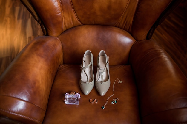 Wedding accessories, bridal shoes on high heels, perfume bottle, jewelry with emerald stone and wedding rings on brown leather armchair