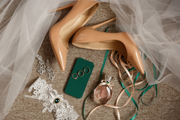 Wedding accessories for bride. bridal shoes on high heels, bridal garter, perfume bottle and three rings