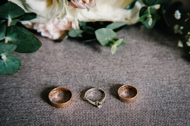 Wedding accessories: flowers, buttonhole, gold wedding rings on rustic sacking, retro brown background. holiday concept. stylish bouquet of flowers of the bride. close up.