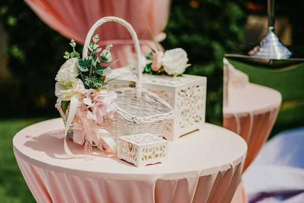 Wedding accessories on the pink table at the ceremony.