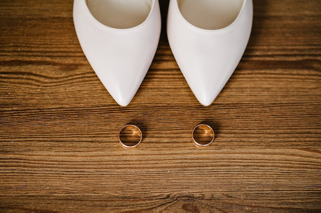 Wedding accessory bride. stylish lacquered beige shoes and gold rings are isolated on table standing on wooden background.  flat lay. top view