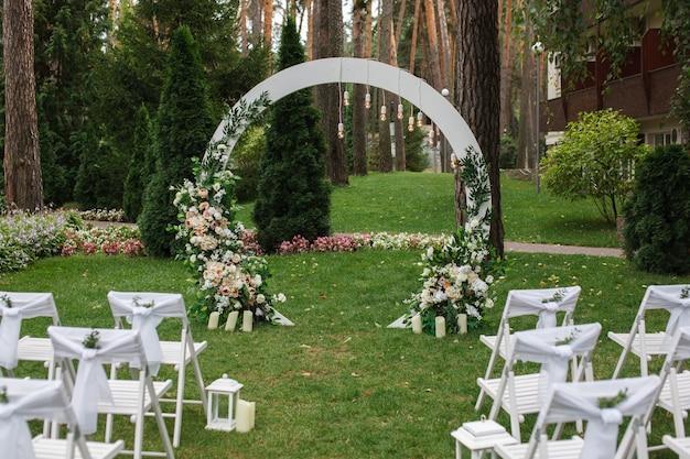 結婚式のアーチと白い木製の椅子が飾られています