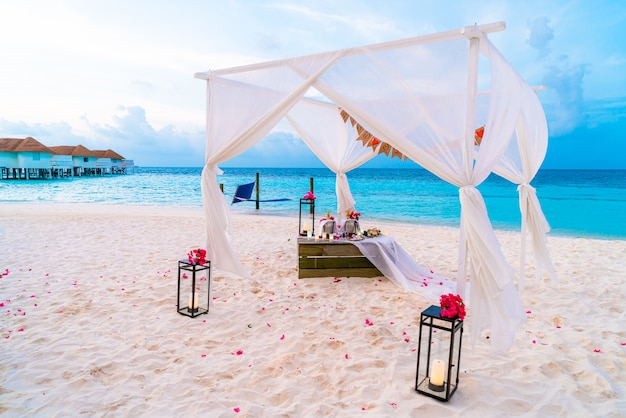 Wedding arch on beach with tropical maldives resort and sea