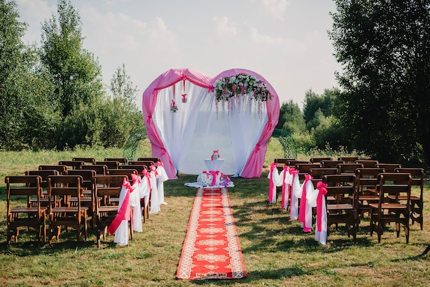 Wedding arch and chairs for ceremony decorated with white and pink flowers