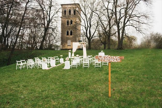 천으로 꽃 야외 장식 웨딩 아치. 아름다운 결혼식을 설정합니다. 정원에서 녹색 잔디밭에 결혼식입니다.