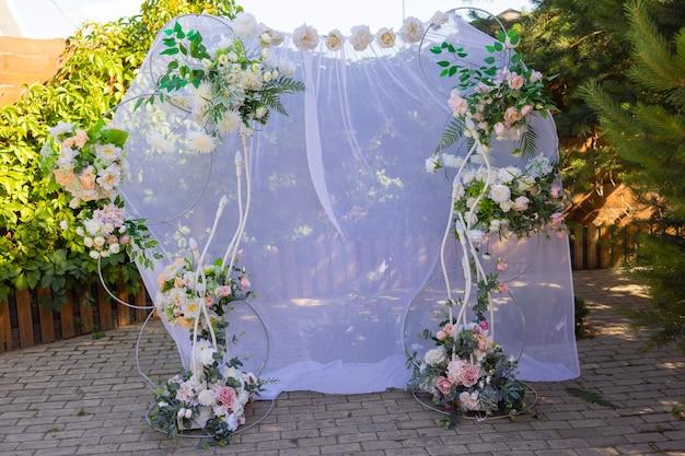 屋外で布や花で飾られた結婚式のアーチ。美しい結婚式のセットアップ。
