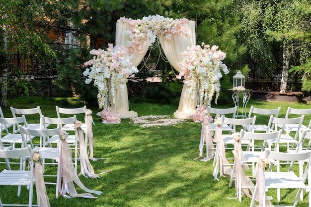 屋外で布や花で飾られた結婚式のアーチ