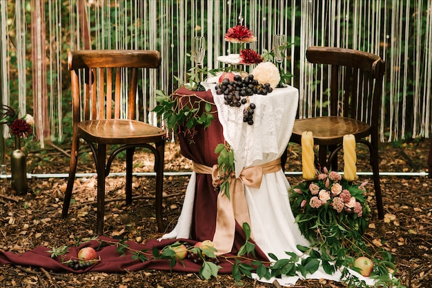 Wedding arch decorated with cloth and flowers outdoors. beautiful wedding set up. wedding ceremony on green lawn in the garden. part of the festive decor, floral arrangement.