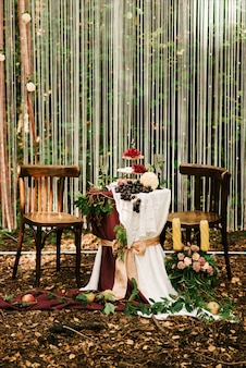 Wedding arch decorated with cloth and flowers outdoors. beautiful wedding set up. wedding ceremony on green lawn in the garden.