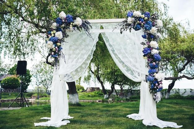 布と花で飾られた結婚式のアーチ。