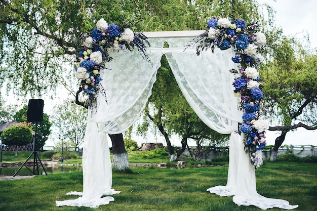 Wedding arch decorated with fabric and flowers.